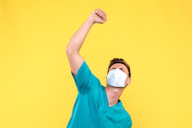 Vista frontale del medico maschio che indossa la maschera sulla parete gialla