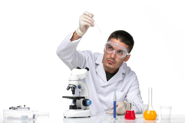 Front view male doctor in white medical suit with gloves and protective sunglasses on a white space