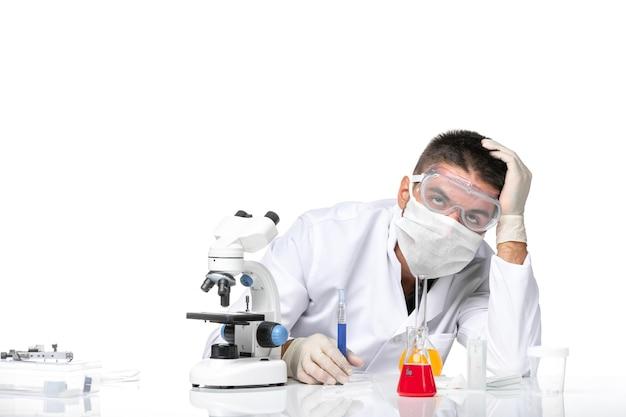 Medico maschio vista frontale in tuta medica bianca con maschera a causa di covid che lavora con soluzioni su uno spazio bianco