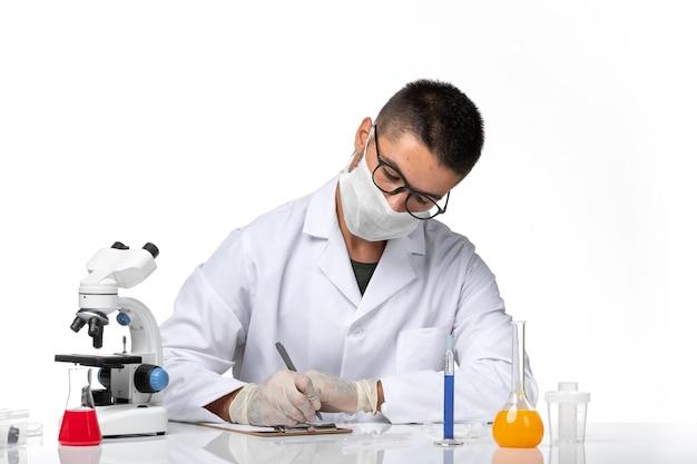 Medico maschio vista frontale in tuta medica bianca con maschera a causa della scrittura covid su uno spazio bianco
