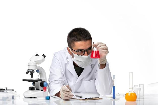 Medico maschio di vista frontale in vestito medico bianco e con la maschera che lavora con la soluzione sullo spazio bianco chiaro