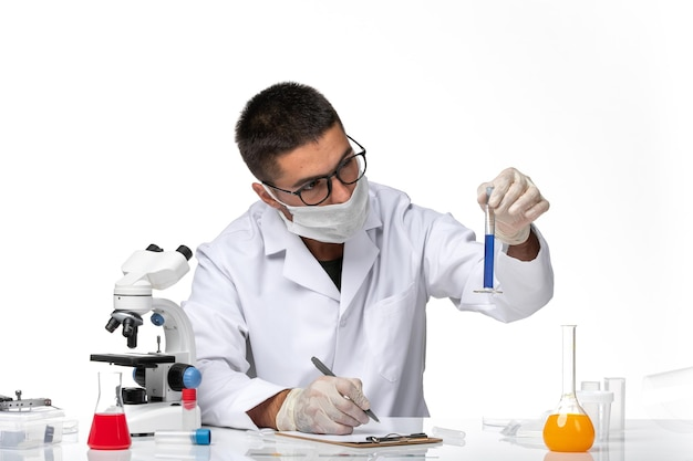 Front view male doctor in white medical suit and with mask working with solution on white desk