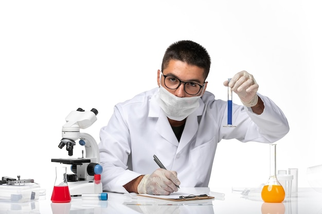 Front view male doctor in white medical suit and with mask working with solution on white space