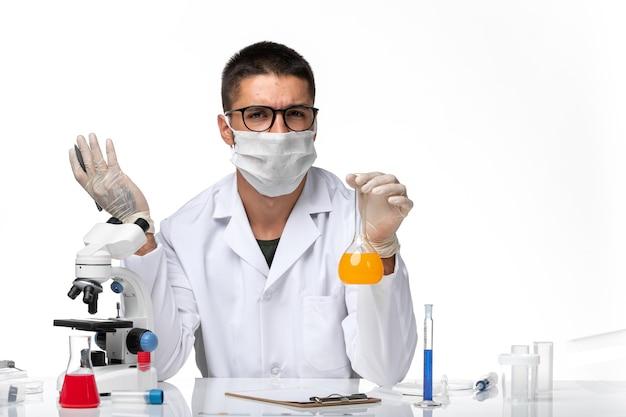 Medico maschio di vista frontale in vestito medico bianco e con la maschera che lavora con le soluzioni sullo spazio bianco