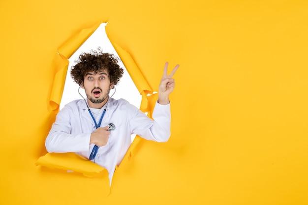 Medico maschio di vista frontale in vestito medico bianco con lo stetoscopio sulla malattia dell'ospedale del virus della medicina di salute del medico di colore strappato giallo
