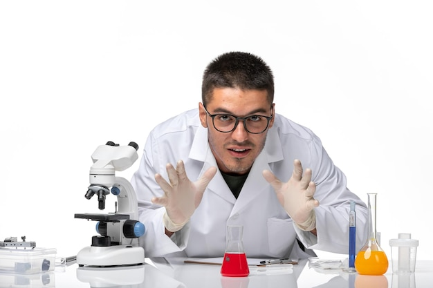 Front view male doctor in white medical suit working with solutions on white floor pandemic virus covid- health