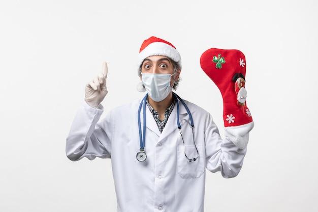 白い机の上の大きな休日の靴下と正面図男性医師covidクリスマスウイルス