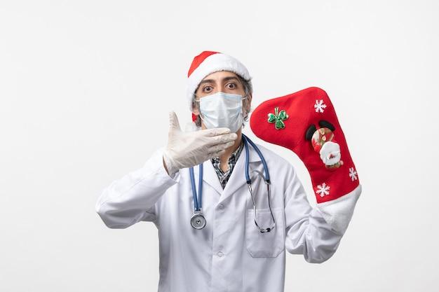 白い床のcovidクリスマスウイルスに大きな休日の靴下を持つ正面図の男性医師