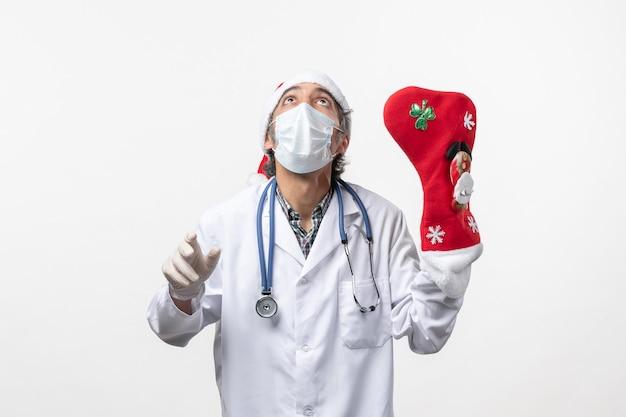 흰 벽 바이러스 covid- 크리스마스에 큰 빨간 양말과 전면보기 남성 의사