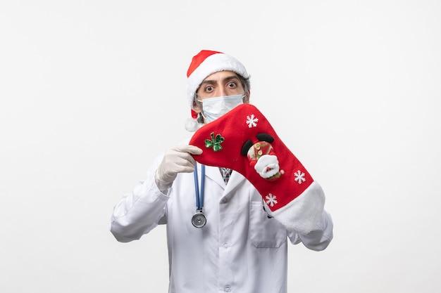 白い机の上の大きな赤い靴下を持った正面図の男性医師ウイルスcovid-クリスマス