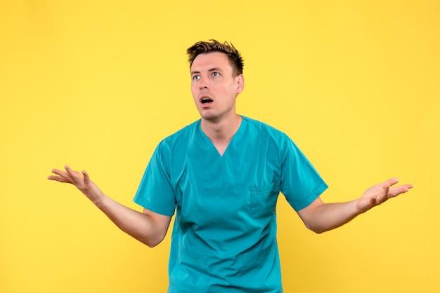 Vista frontale del medico maschio con espressione confusa sulla parete gialla