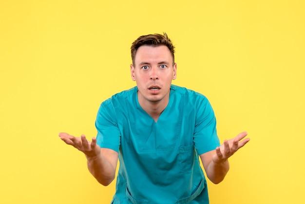 Vista frontale del medico maschio con la faccia confusa sulla parete gialla