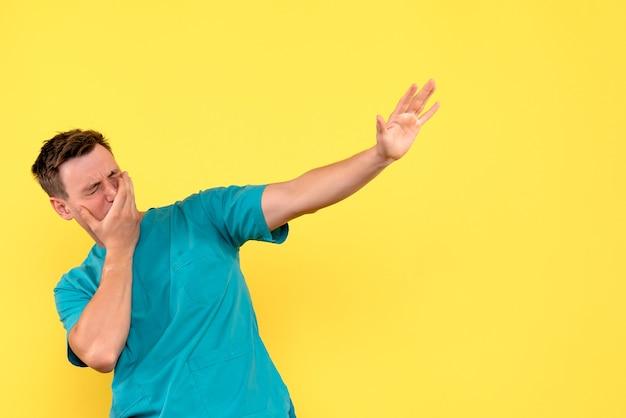 Vista frontale del medico maschio con espressione di pianto sulla parete gialla
