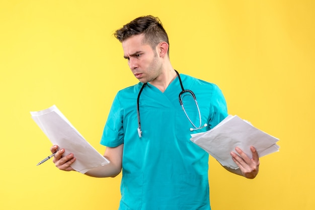 Front view of male doctor with documents on yellow wall