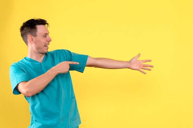 Vista frontale del medico maschio con espressione eccitata sulla parete gialla