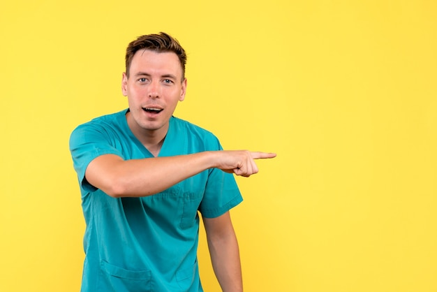 Front view of male doctor with excited expression on yellow wall