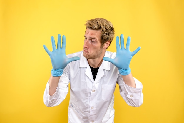 Front view male doctor with gloves on a yellow background medic covid- health hygiene