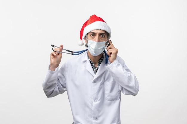 白い壁の休日のcovidパンデミックウイルスのマスクと正面図男性医師
