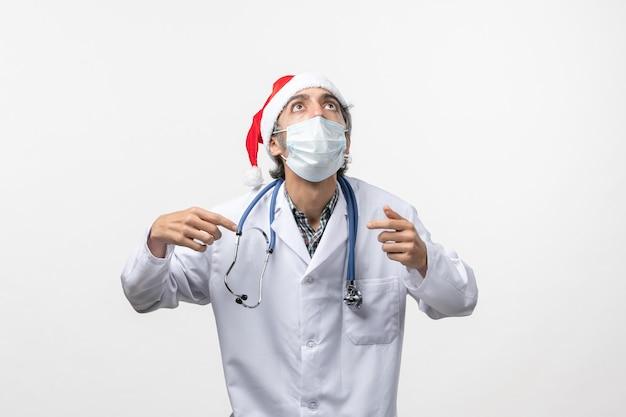 白い机の上のマスクを持つ正面図男性医師休日covidパンデミックウイルス