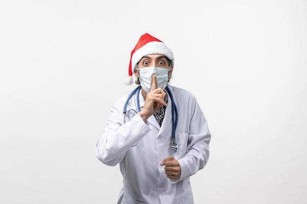 白い机の上のマスクを持つ正面図男性医師休日パンデミックcovidウイルス