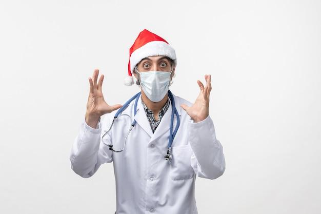 白い机の上のマスクを持つ正面図男性医師パンデミックcovidホリデーウイルス