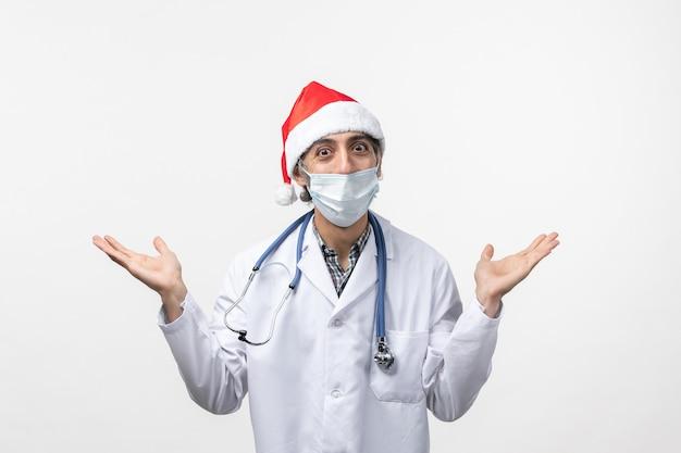 흰 벽에 마스크가있는 전면보기 남성 의사 휴일 covid 유행성 바이러스