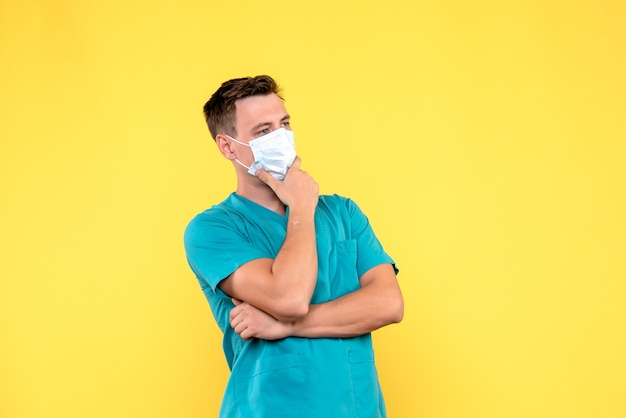 Front view of male doctor with mask thinking on yellow wall