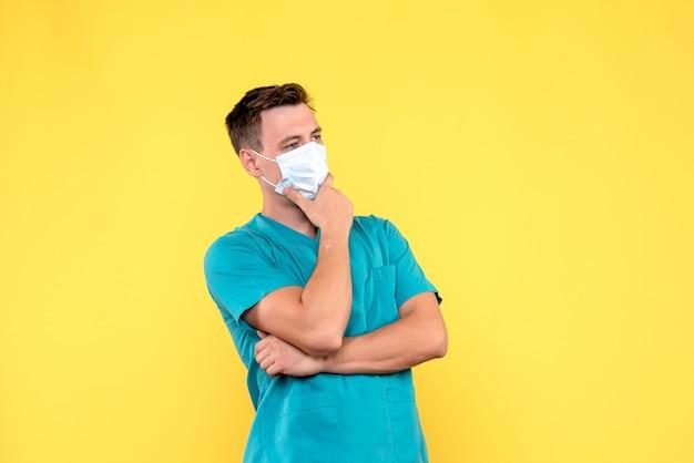 Vista frontale del medico maschio con maschera pensando sulla parete gialla