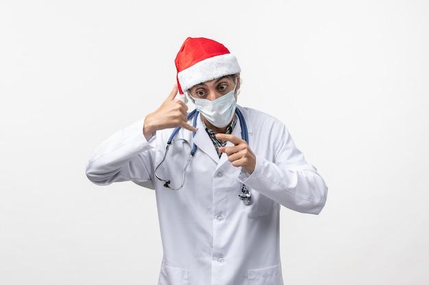 Medico maschio vista frontale con maschera sul virus pandemico vacanza covid scrivania bianca
