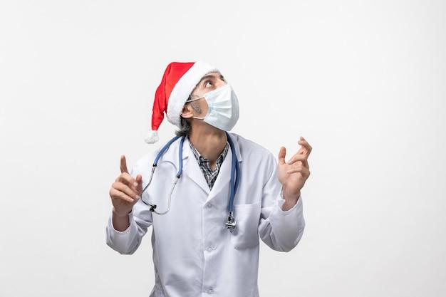 Medico maschio di vista frontale con la maschera sul covid pandemia di vacanza del virus del pavimento bianco