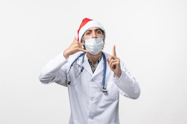 Medico maschio vista frontale con maschera su un virus pandemico vacanza covid muro bianco