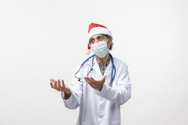 Medico maschio vista frontale con maschera su un virus covid pandemia vacanza muro bianco