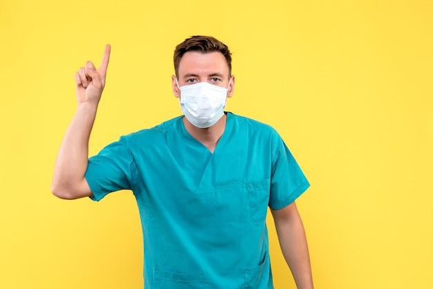 Vista frontale del medico maschio con maschera sulla parete gialla