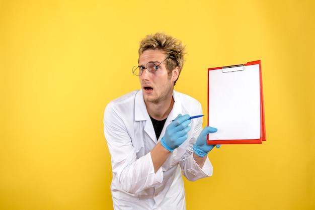 黄色の背景の健康人間のcovidmedicに関するメモと正面図男性医師