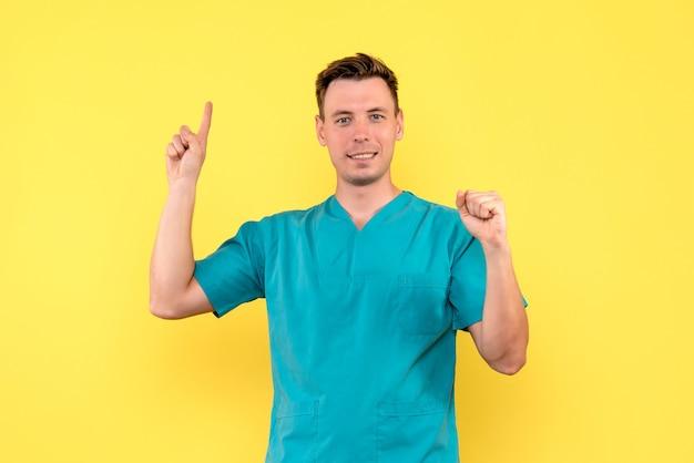 Vista frontale del medico maschio con espressione sorridente sulla parete gialla