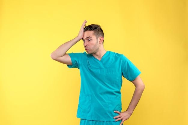 Vista frontale del medico maschio con la faccia dispiaciuta sulla parete gialla