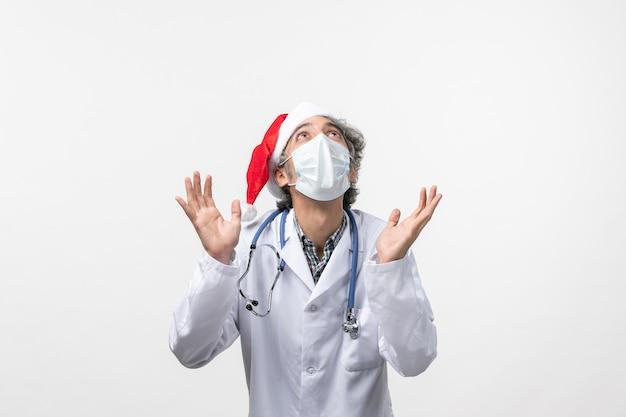 白い机の上の滅菌マスクと正面図男性医師covidウイルスパンデミック新年