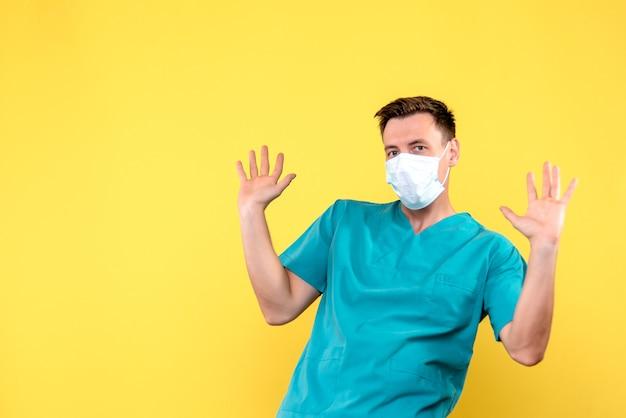 Vista frontale del medico maschio con maschera sterile sulla parete gialla