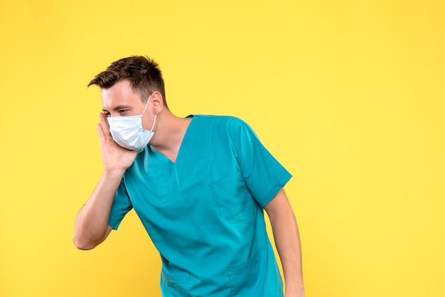 Front view of male doctor with sterile mask on yellow wall