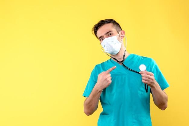 Vista frontale del medico maschio con lo stetoscopio e la maschera sulla parete gialla