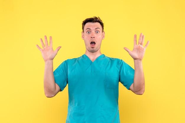 Vista frontale del medico maschio con espressione sorpresa sulla parete gialla