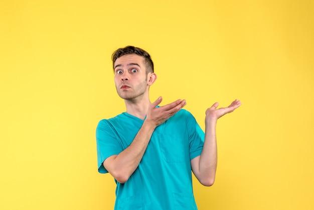 Vista frontale del medico maschio con la faccia sorpresa sulla parete gialla