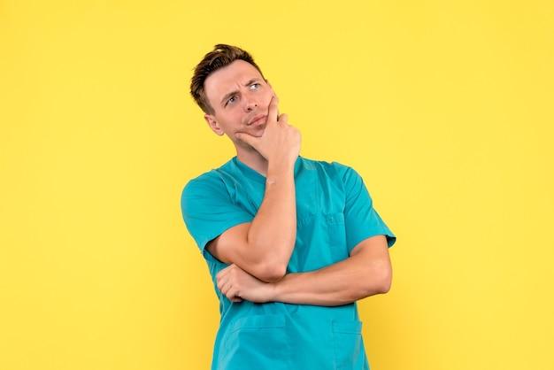 Vista frontale del medico maschio con espressione di pensiero sulla parete gialla