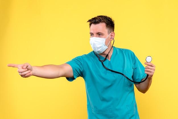 Vista frontale del medico maschio con tonometro e maschera sulla parete gialla
