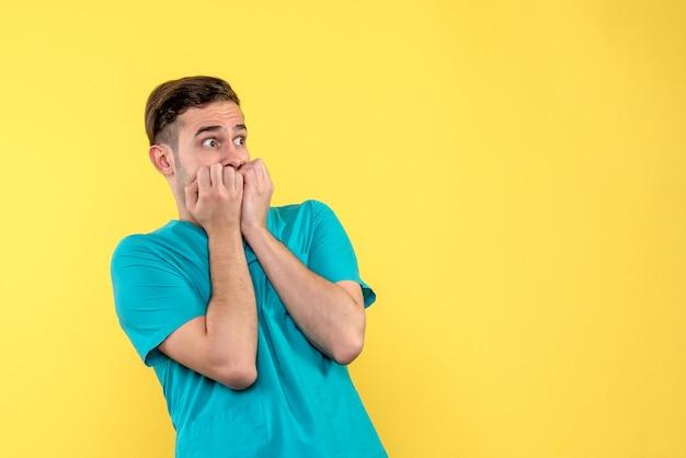 Vista frontale del medico maschio con la faccia molto spaventata sulla parete gialla