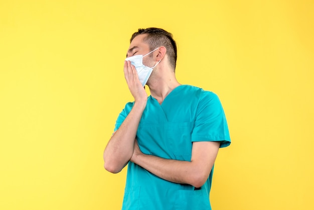 Vista frontale del medico maschio che sbadiglia in maschera sterile sulla parete gialla