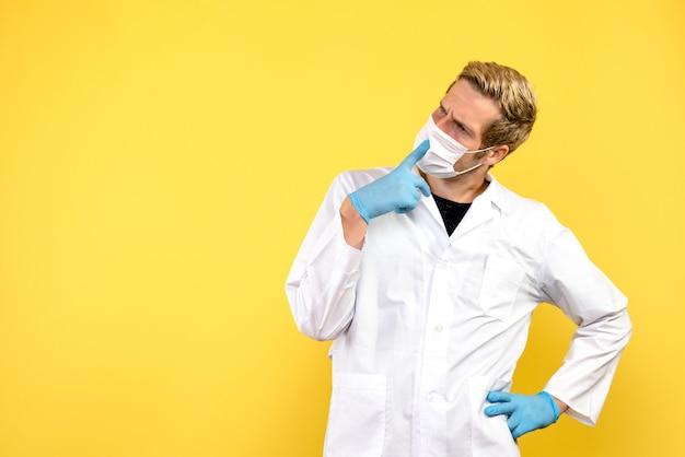 Vista frontale medico maschio su sfondo giallo salute medico pandemia covid