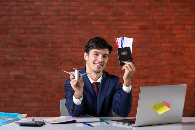 Front view of male engineer sitting behind his working place in suit holding toy airplane work plan contractor business job occupation corporate flight tourism project