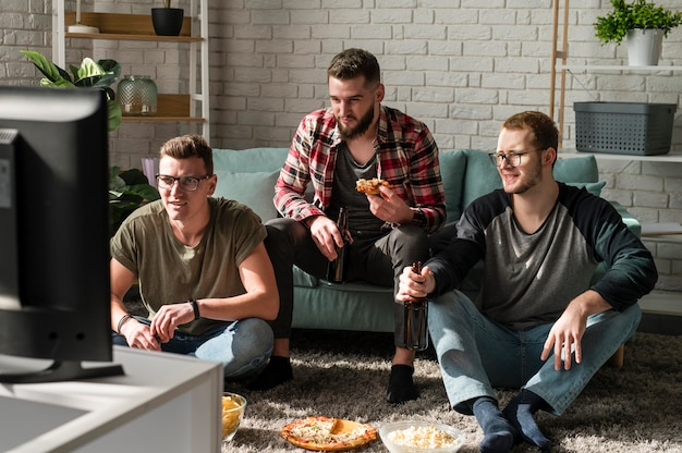 Front view of male friends having pizza with beer and watching sports on tv
