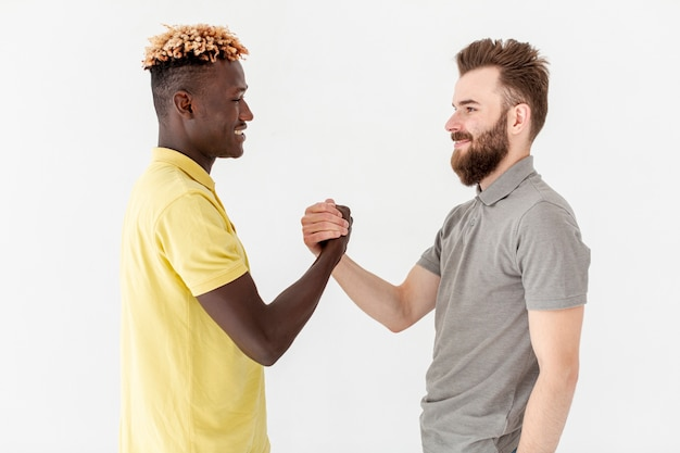 Front view male friends shaking hands